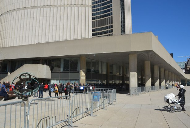 The corner of Toronto City Hall with a long line up of people waiting to get inside.