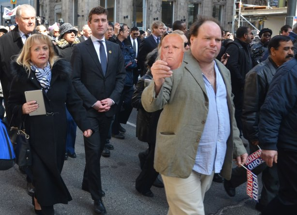 People walking in a procession including a man holding a Rob Ford mask