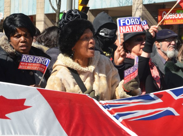 a man in a black and white mask stands behind some women waving ford nation flags.