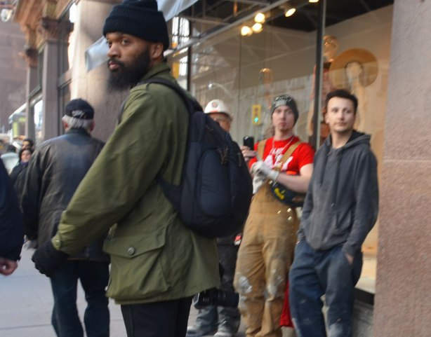 A black man with beard and moustache turns to look back, three young men in work clothes stand against the storefront beside and behind him.