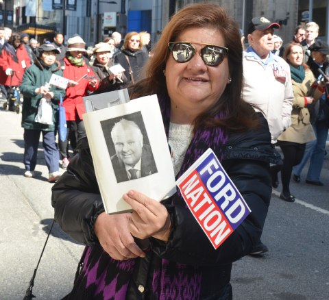 a woman wearing sunglasses and holding two things, a photo of Rob Ford, and a small Ford Nation flag