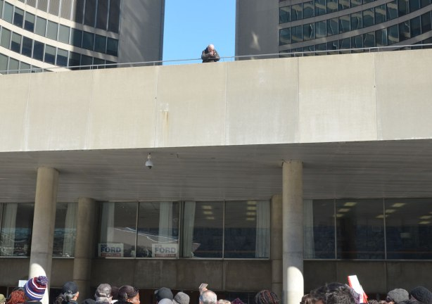 A lone cameraman stands on the upper level at City Hall outside, taking pictures of the people below.