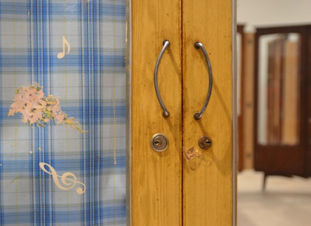 part of an art installation by Chinese artist Song Dong using vintage wooden wardrobe doors with mirrors and curtains, reflections, door handles, key holes and a curtain that is a blue and white plaid and has musical notes on it.