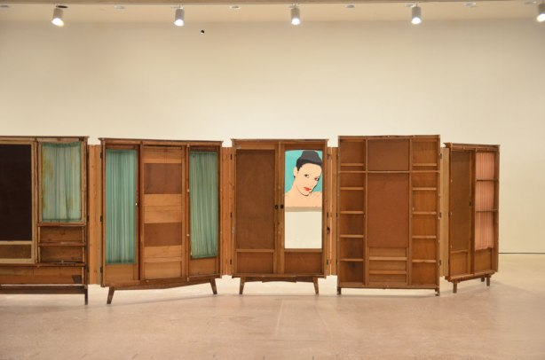 part of an art installation by Chinese artist Song Dong using vintage wooden wardrobe doors with mirrors and curtains, reflections. through one of the windows there is a painting of Karen Kain on the wall