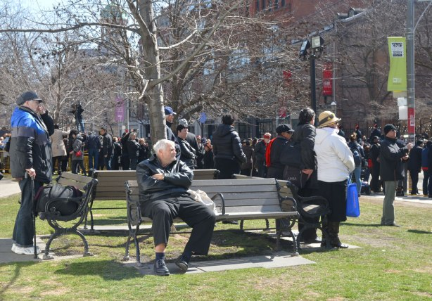 An older man sits on a bench in front of St. James cathedral while other people stand around, watching the procession for Rob Ford's funeral