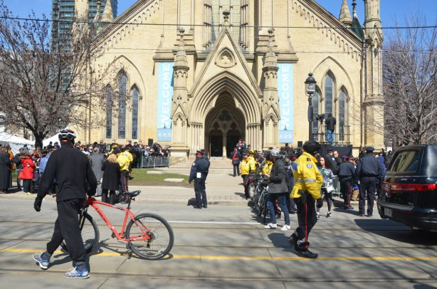 From King St., the view of St. James cathedral front doors, lots of people and police in yellow jackets in the picture as well as a man walking his bike
