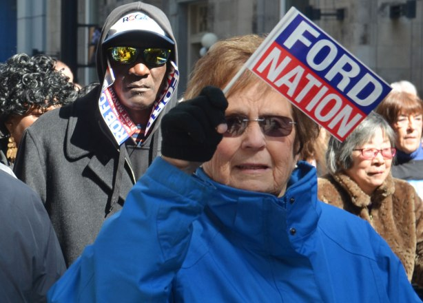 An older woman waves a little Ford Nation flag while the man behind her has used Ford Nation signs in lieu of a scarf. He is wearing reflective sunglasses too.