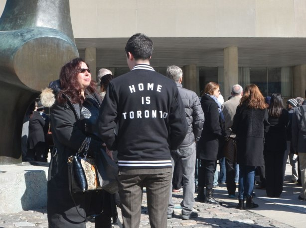 Two people in front of the Archer sculpture at Nathan Phillips Square, a man and a woman. The mans back is turned towards the camera. He is wearing a black jacket with the words 'Home is Toronto' in white letters.