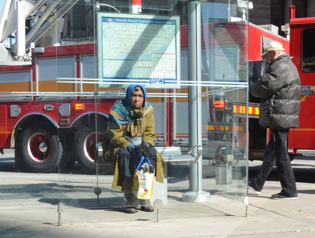 An older woman sits on a bench inside a TTC bus shelter. A fire truck is behind her.