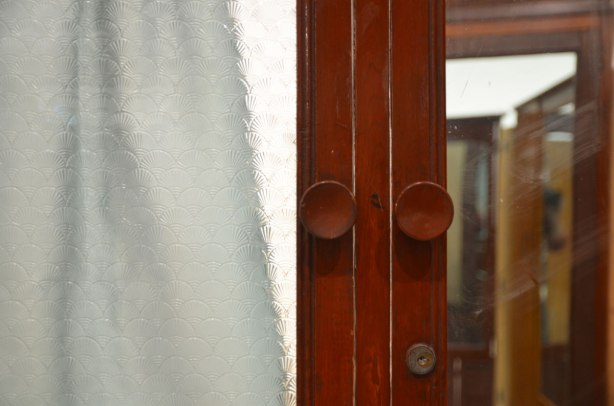 part of an art installation by Chinese artist Song Dong using vintage wooden wardrobe doors with mirrors and curtains, reflections, door knobs and frosted glass and a white curtain