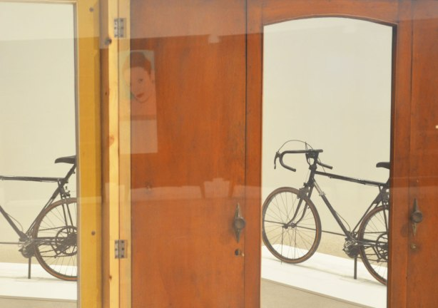 part of an art installation by Chinese artist Song Dong using vintage wooden wardrobe doors with mirrors and curtains, reflections, through two of the windows there is a bike