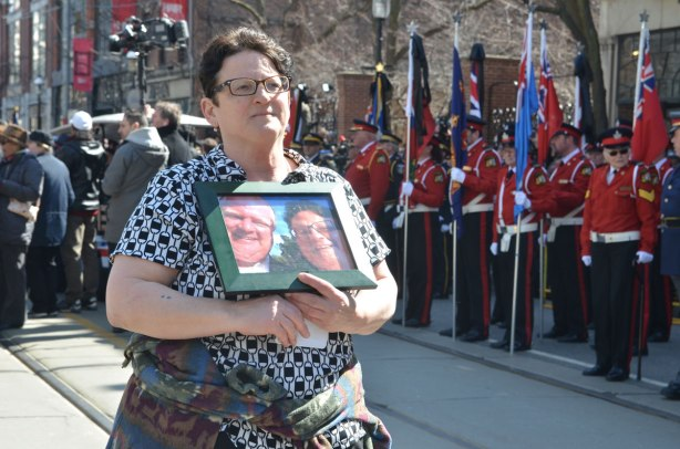 a woman holds a framed photo of a selfie of her and Rob Ford