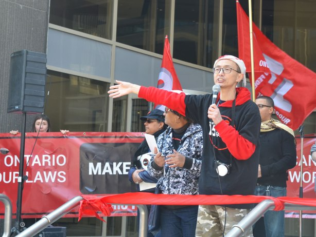 photographs taken at a rally and protest in support of a $15 minimum wage, The Fight for 15 and fairness - one of the leaders, a young Asian man, gives a speech