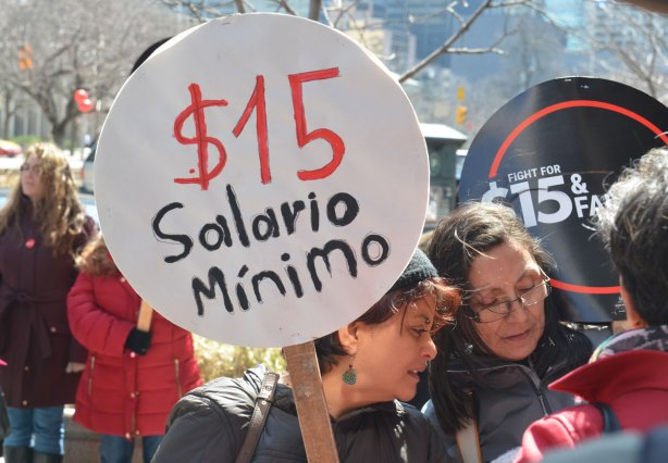photographs taken at a rally and protest in support of a $15 minimum wage, The Fight for 15 and fairness - two women are talking together. One holds a sign that says $15 salario minimo (Spanish)