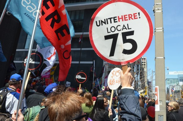 "photographs taken at a rally and protest in support of a $15 minimum wage, The Fight for 15 and fairness - people holding flags and one person holding a sign that says ""Unite here local 75"""