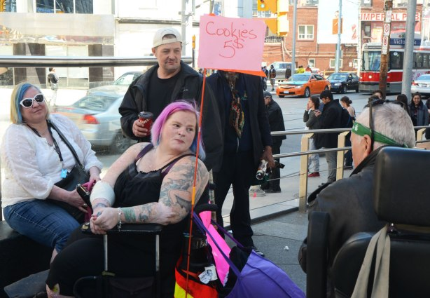 People at Yonge Dundas Square in Toronto celebrating 420 day - a young woman in an electric wheelchair with bright pink hair is selling cookies for $5