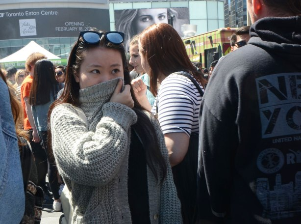 People at Yonge Dundas Square in Toronto celebrating 420 day - a young woman walks through the crowd, holding part of her grey sweater over her nose