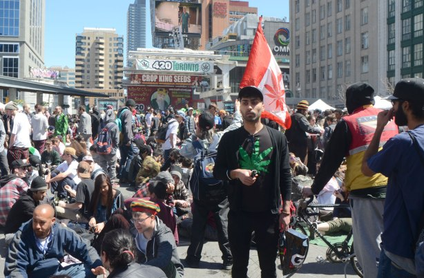 People at Yonge Dundas Square in Toronto celebrating 420 day - a young man stands amidst those who are sitting on the ground