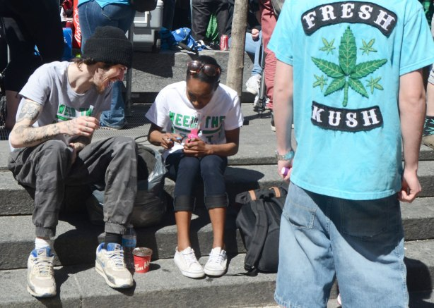 People at Yonge Dundas Square in Toronto celebrating 420 day - two people sitting together and talking, a man's back is to the camera and on the back of his tshirt are the words fresh kush and a picture of a cannabis leaf
