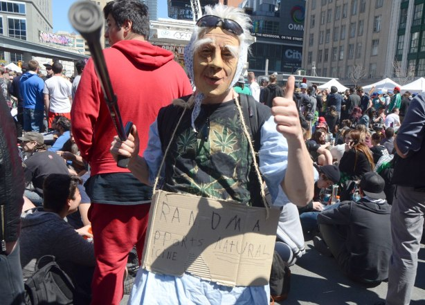 a person with an old person mask and a carboard sign that says grandma likes her natural medicine, is waving a cane at the camera