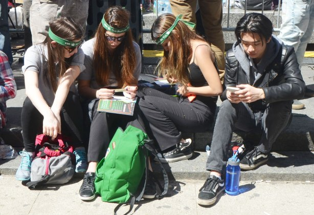 three young women with long hair and green headbands are sitting together. A young man on a cellphone is sitting beside them.
