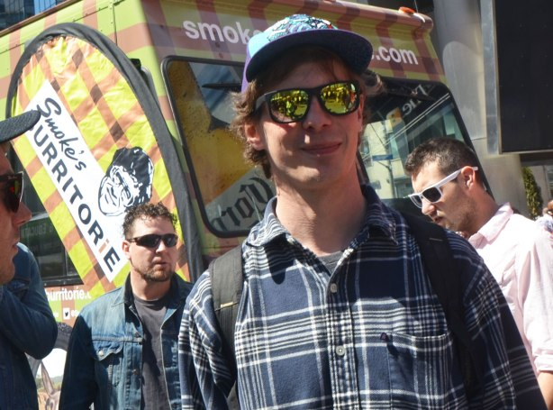 People at Yonge Dundas Square in Toronto celebrating 420 day - 4 young men, one of whom has yellow reflective sunglasses on.