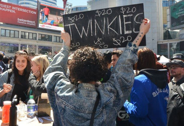 People at Yonge Dundas Square in Toronto celebrating 420 day - a young woman in a jean jacket is holding up a black sign advertising twinkies for sale.