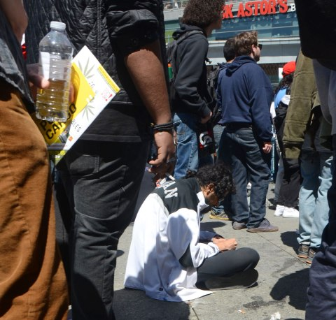 People at Yonge Dundas Square in Toronto celebrating 420 day - a young man sits on the ground while others around him are standing