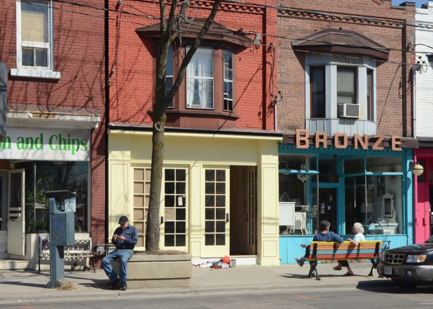 Looking across the street at a man sitting on the edge of a concrete planter for a tree as well as a multicoloured striped bench with two women sitting on it. They are in front of two storey brick buildings with stores on the bottom level and apartments on the top. One of the stores is Bronze.