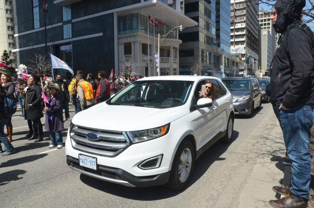 photographs taken at a rally and protest in support of a $15 minimum wage, The Fight for 15 and fairness - a white car passes by the rally, the woman driver leans out her window to take a picture with her cellphone