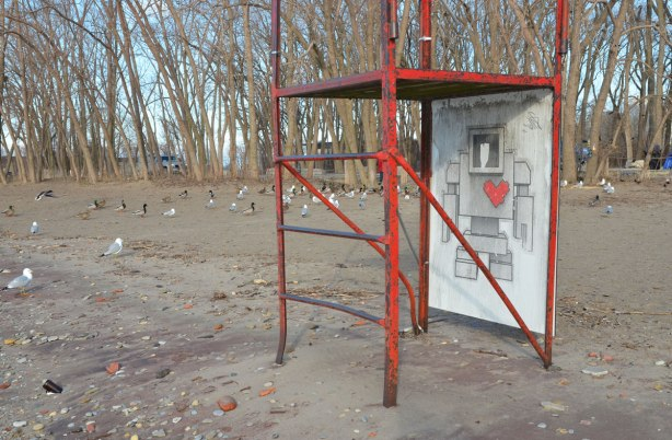 an empty red metal frame lifeguard chair on the beach in early spring, no leaves on the trees. Cherry Beach, Lake Ontario. There is a large lovebot wheatpaste on the lifeguard chair.