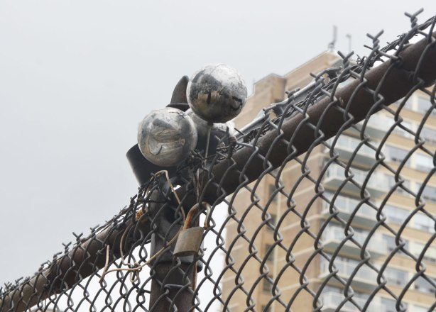 three silver Christmas ball ornaments are attached to the top of a chain link fence
