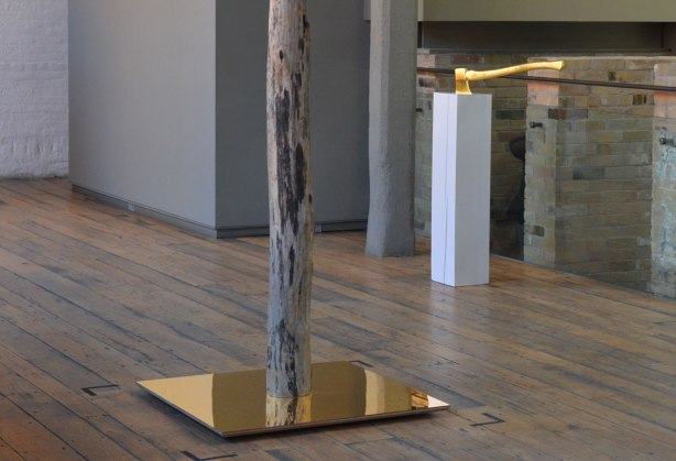 picture taken inside an art gallery - a tree trunk stands in the middle of a gold toned mirror, in the background, a gold plated (or gold colured) axe with its blade in the top of a white rectanguar column