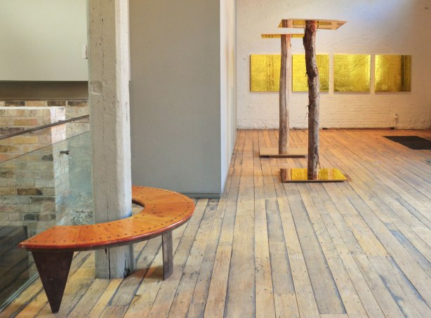 picture taken inside an art gallery - a tree trunk stands in the middle of a gold toned mirror, also a mirror is on the top of each trunk, in the background are four panels of wrinkled gold