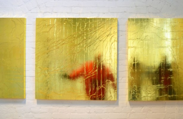 three square panels of reflective gold, wrinkled, material with reflections of people in them.