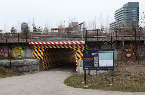 pedestrian underpass under railway tracks that has been painted in bright stripes, yellow, red and black. The left of it is a large yellowlovebot and to the right is a sign with a map and a description of the Don Pathway, part of the Pan Am Path.