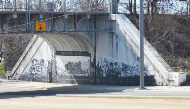 mural in black, white, and grey about the first railway in Ontario, 1853, that was built here, and where the railway still runs as the GO line to Aurora - a photo of the mural from across the street, with its three parts, the words St. Clair West on the left, the locomotive in the middle and the railway workers on the right