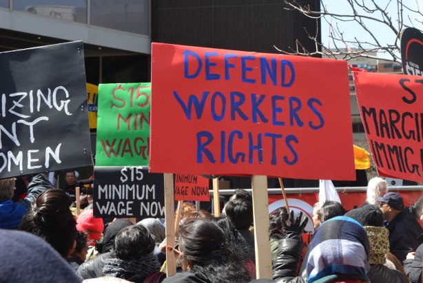 "photographs taken at a rally and protest in support of a $15 minimum wage, The Fight for 15 and fairness - people holding signs that says ""defend workers rights"" and ""fifteen dollar minimum wage now"""