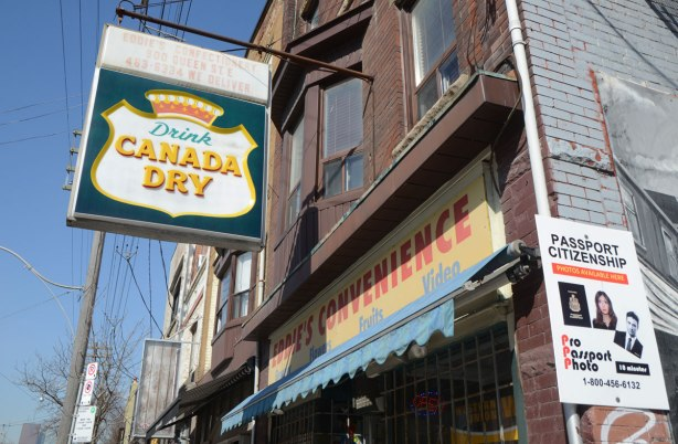 An older Canada Dry advertisement sign hangs over the entrance to Eddies Convenience Store on Queen St East.
