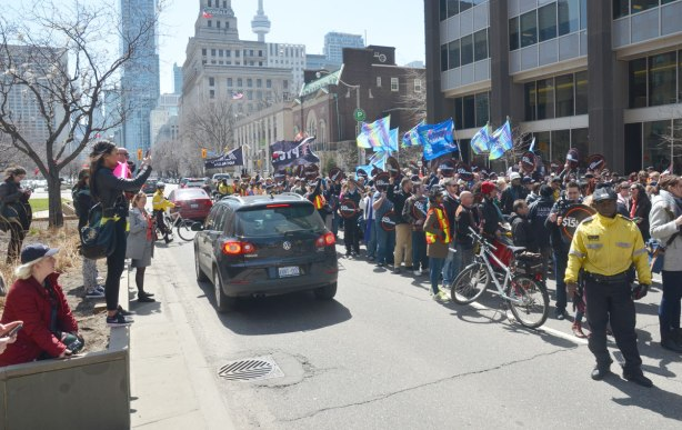 cars driving past the protest on University Ave., people lined up on the boulevard taking pictures of the rally
