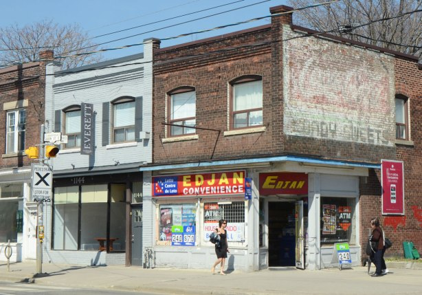 On a corner, Edjan Convenience Store with people walking past it. On the side of the upper floor of the two storey brick building is a ghost sign advertising coca cola and Coady Sweets. At the corner of Coady and Queen St. East in Leslieville Toronto