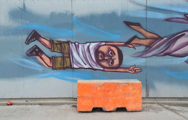 the end of a mural, a man is sideways, arm above his head, painted on a mural, a large orange concrete block is in front of the wall, an empty Tim Hortons cup (Timmies cup) is on the ground.