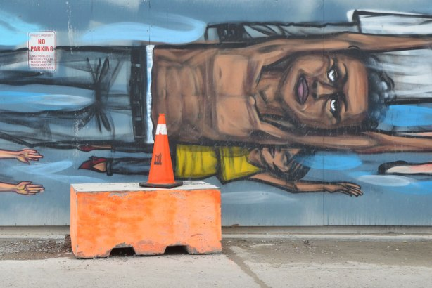 Two people painted flying sideways on a mural, a brown man with no shirt on and a much smaller person below him with a yellow T-shirt. An orange concrete block is on the sidewalk in front of the mural along with an orange and white traffic cone