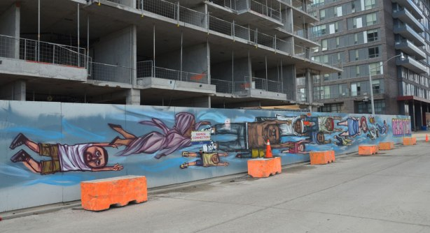 a long mural by elicser painted on hoardings around a building under construction. People flying past in the mural