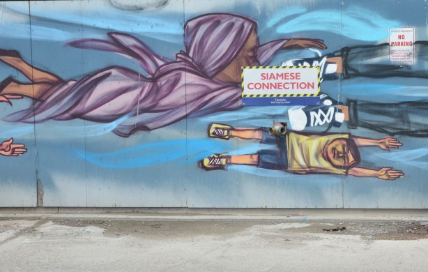 part of a mural of flying people by elicser, a woman in a light purple dress and head scarf as well s a boy in beige Tshirt and blue shorts
