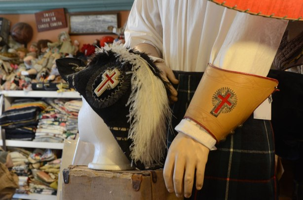 An old black military hat with a white feather in it sits on a head mannequin. Beside it is another mannequin wearing a tartan kilt and a white shirt. The shirt has a brownish leather cuff with a red cross on it.