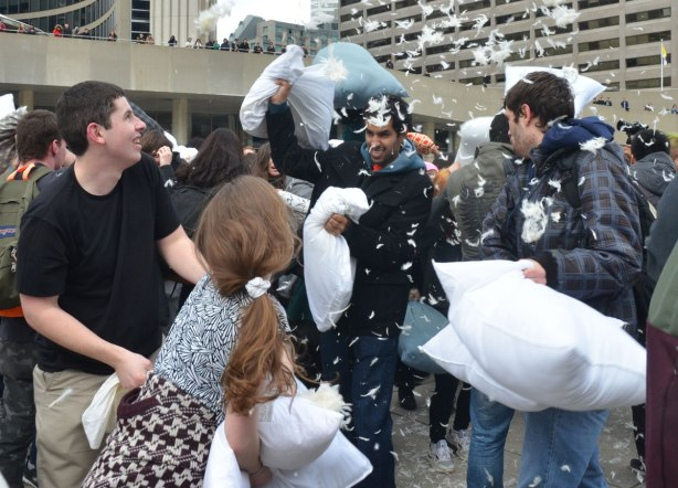 feathers go flying as pillows break during a pillow fight amongst a crowd of people