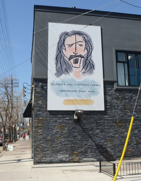 A mural of Frank Zappa on the upper floor of a two storey building. Also includes the words Stupidity has a certain charm, ignorance does not.