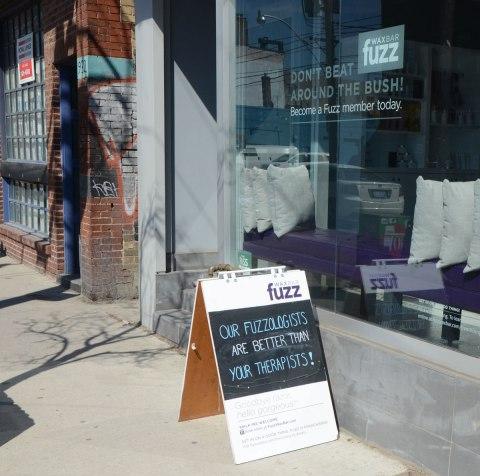 board outside Fuzz salon.