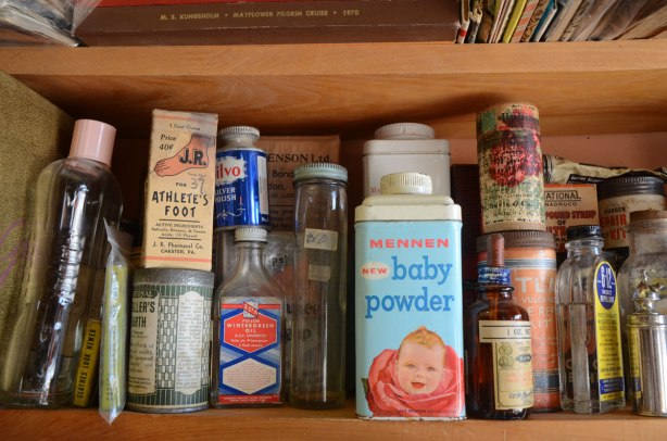 A small section of shelf in a store selling vintage items, on this shelf are old drug store and household products such as wintergreen oil, silvo silver polish, baby powder, athletes foot treatment,